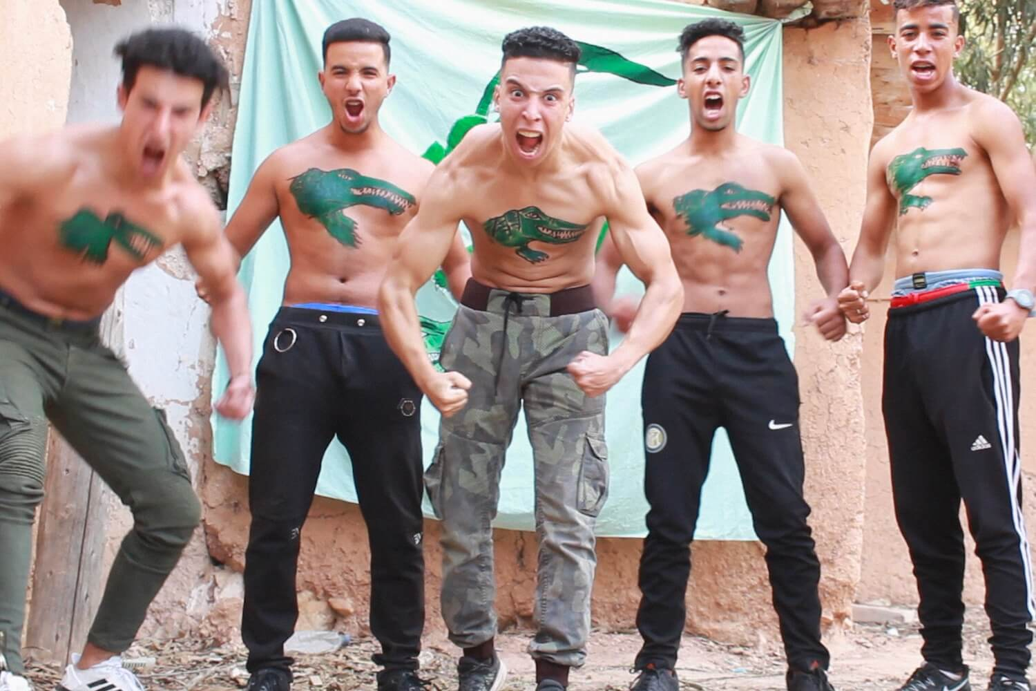 A group of shirtless Moroccan men with crocodiles painted on their chests flex and yell at the camera